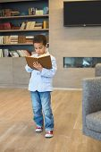 Little mulatto boy in a striped jacket and sneakers read a book in library