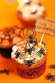 Halloween cupcakes with decoration over orange background