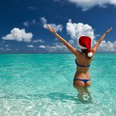 Woman in santa's hat in bikini at tropical beach