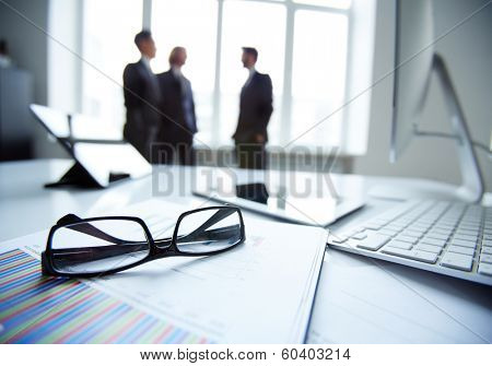 Technological devices, eyeglasses and financial document at workplace on background of three busines poster