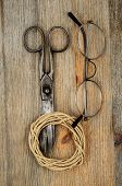 Old Scissors, Glasses And Hank Of Packthread Over Wooden Texture