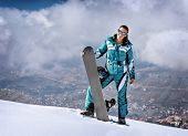 Sportive woman standing on the top of mountain with snowboard in hands, active wintertime holidays, extreme lifestyle concept