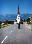 Traveling of bikers along Alpine mountains, group of motorcyclists riding across mountainous town, extreme sport, active lifestyle, happy vacation concept