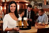Portrait of happy young woman serving beer in bar, looking at camera smiling.