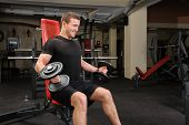Handsome young man doing Dumbbell Biceps workout in gym. Motion blur at arms.