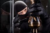 Angry burglar wearing black woollen mask, considering vase over black