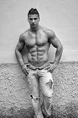 Attractive Young Man Shirtless With Jeans Leaning Against A Wall