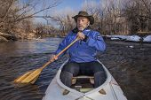 senior canoe paddler in a decked expedition canoe on the Cache la Poudre River, Fort Collins, Colora