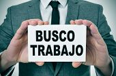 a man wearing a suit holding a signboard with the text busco trabajo, looking for a job written in s