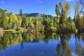 Colourful Mountains Of Colorado Reflecting In A Lake During Foliage Season