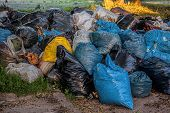 stock photo of landfill  - A landfill with a colorful rubbish sacs