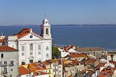 Alfama District with Santo Estevao Church and the Tagus River estuary seen from Miradouro de Santa L