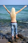 foto of top-less  - Free woman in jeans near the sea - JPG