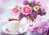 Beautiful spring flowers in vase and cup of tea
