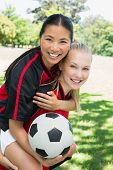 Portrait of happy female soccer player piggybacking teammate at park