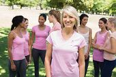 Portrait of confident woman supporting breast cancer awareness with friends in background at park