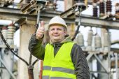 stock photo of substation  - Electrician in electrical substation near to high - JPG