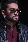 closeup portrait of a bearded casual young man with sunglasses, looking away from the camera. on a black background