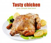Whole roasted chicken with vegetables on plate, isolated on white