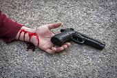 man's hand lying on the floor after suicide with a gun