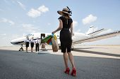 stock photo of diva  - Full length rear view of woman carrying shopping bags while walking towards private jet at airport terminal - JPG