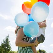 Side view of mother and daughter with helium balloons in park