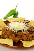 Mexican food: cheesy chili with meat served with nachos