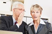 Business man in the office whispering a secret into ear of surprised woman
