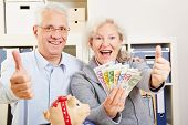 Happy senior couple with fan of Euro money holding thumbs up