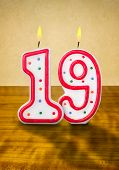 Burning birthday candles number 19 on a wooden background