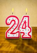 Burning birthday candles number 24 on a wooden background