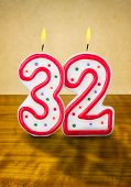 Burning birthday candles number 32 on a wooden background