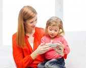 family, children, parenthood, technology and internet concept - happy mother and daughter with smart