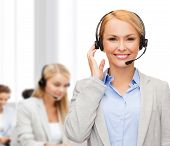 business, technology and call center concept - friendly female helpline operator with headphones at office