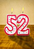 Burning birthday candles number 52 on a wooden background