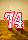 Burning birthday candles number 74 on a wooden background