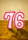 Burning birthday candles number 76 on a wooden background