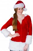 Pretty girl in santa costume smiling at camera on white background