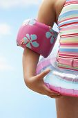 Midsection of girl wearing inflatable ring and water wings against sky