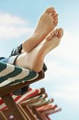 Low section of woman's feet relaxing on deckchair at beach
