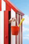 Woman's hand holding bucket and spade in beach cabin