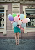 Happy romantic fashion girl with colorful balloons, outdoors