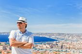 Man In A Hat And Sunglasses Posing Against The City Of Marseille
