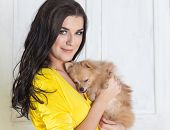 Beautiful Brunette Woman In Yellow Dress With Small Dog In Hands