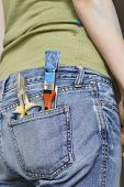Closeup midsection of a woman with paintbrush and hand tools in back denim jeans pocket
