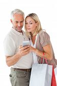 Happy couple holding shopping bags and smartphone on white background