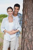Portrait of a smiling young couple standing by tree trunk