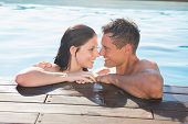 Smiling romantic young couple in swimming pool on a sunny day
