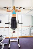 Rear view of a fit young woman doing pull ups at the gym