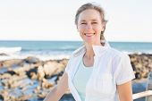 Casual woman smiling at camera by the sea on a sunny day